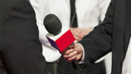 photo of man being interviewed with microphone in front of him